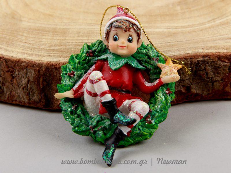 Χαρούμενο ξωτικό που κάθεται σε ένα εντυπωσιακό χριστουγεννιάτικο στεφάνι