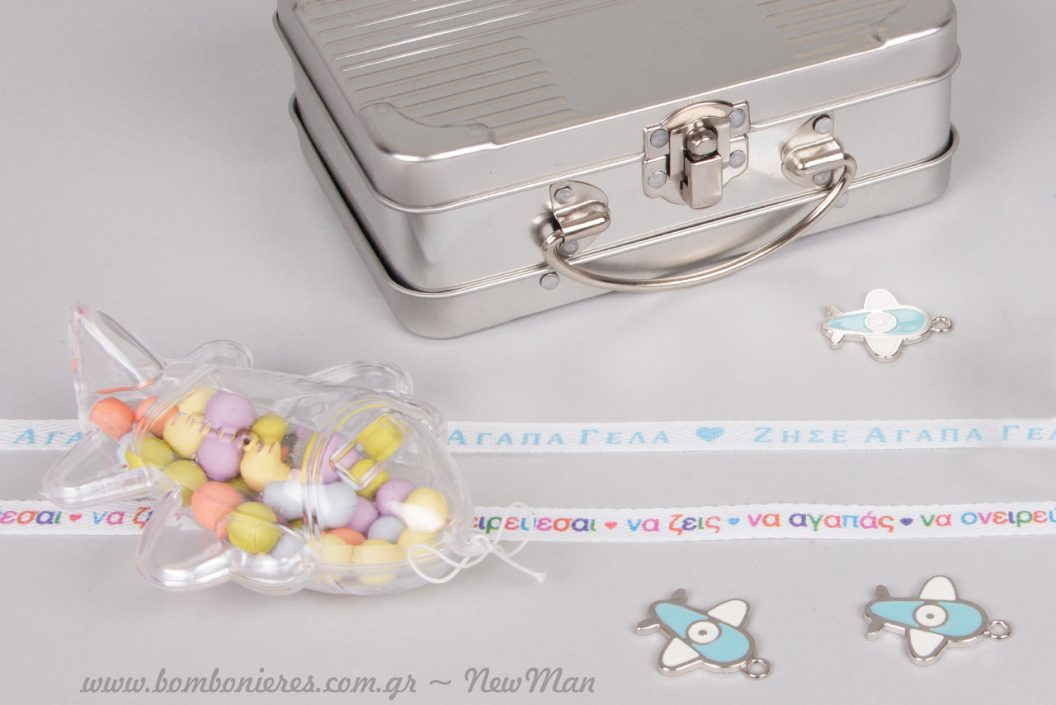 Κρεμαστό πλαστικό κουτί-αεροπλάνο και μεταλλικό βαλιτσάκι σε ασημί απόχρωση για τις πιο ταξιδιάρικες μπομπονιέρες.