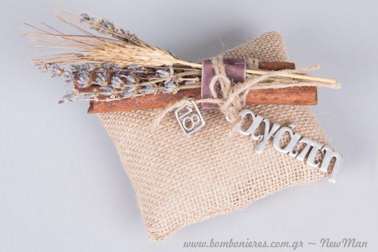 Γούρι σε μαξιλαράκι από λινάτσα διακοσμημένο με αποξηραμένα άνθη, κανέλλα και μεταλλικές διακοσμητικές ευχές.