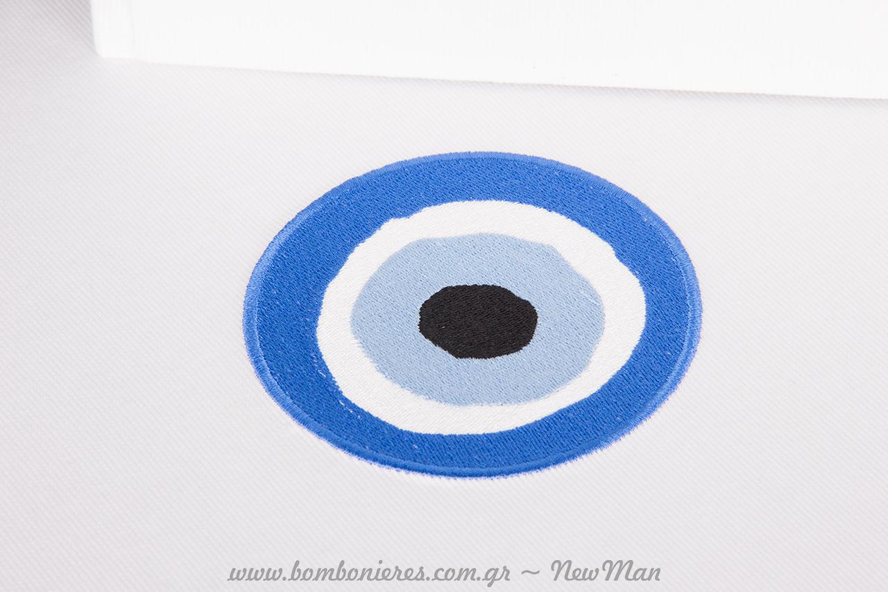 Κεντημένο (ανάγλυφο) υφασμάτινο μάτι πάνω στην καπελιέρα ή στο βιβλίο ευχών.
