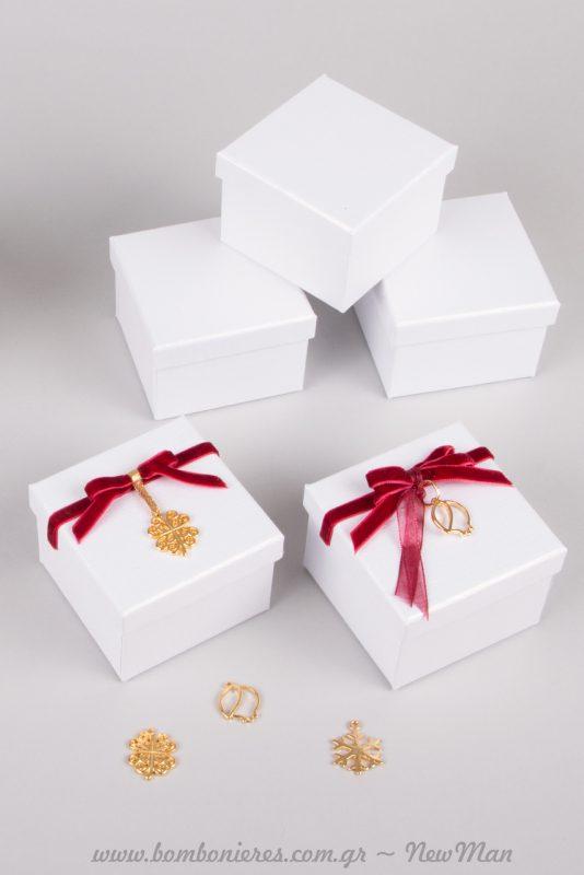 Μπομπονιέρα σε λευκό ή εκρού κουτί (7 x 7 x 5cm) με μπορντό και χρυσαφένια διακοσμητικά στοιχεία.