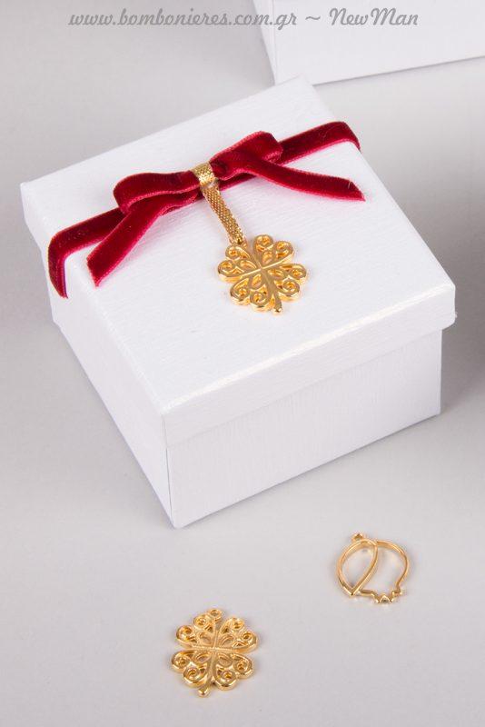 Μπομπονιέρα σε κουτί με διακοσμητικό τετράφυλλο τριφύλλι σε χρυσαφένια απόχρωση.
