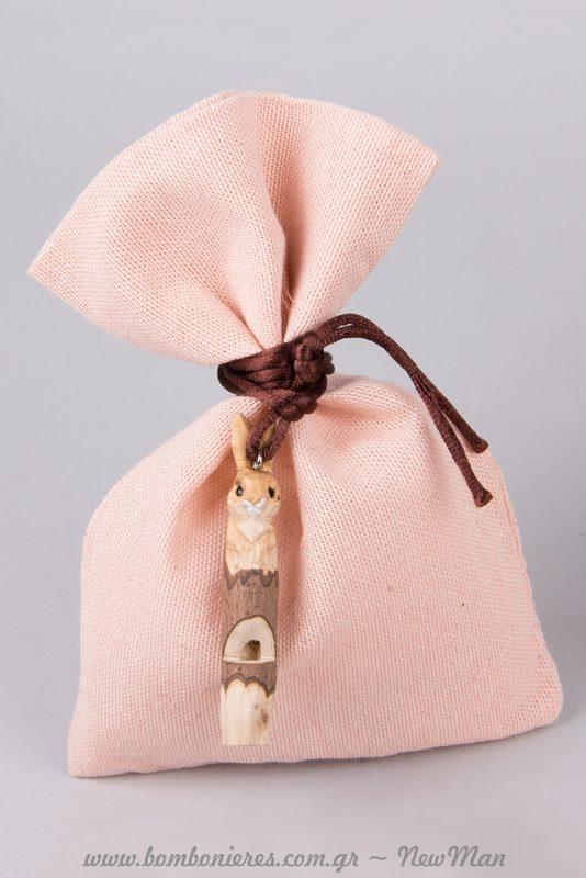 Ροζ υφασμάτινο πουγκί με διακοσμητικό τη ξύλινη σφυρίχτρα-λαγουδάκι.