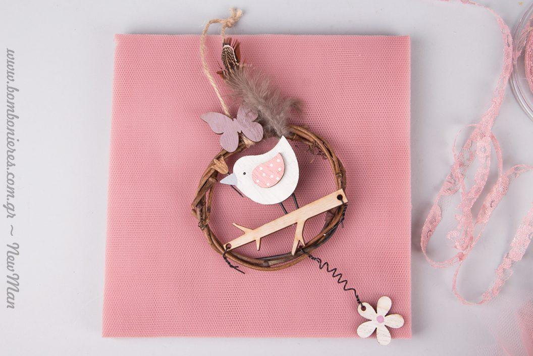 Κρεμαστή κοριτσίστικη μπομπονιέρα με πουλάκι σε κλαδί (στεφάνι) και ροζ πινελιές.