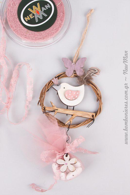 Ξύλινο πουλάκι σε κλαδί (στεφάνι) με ροζ λεπτομέρειες για την κρεμαστή κοριτσίστικη μπομπονιέρα σας.