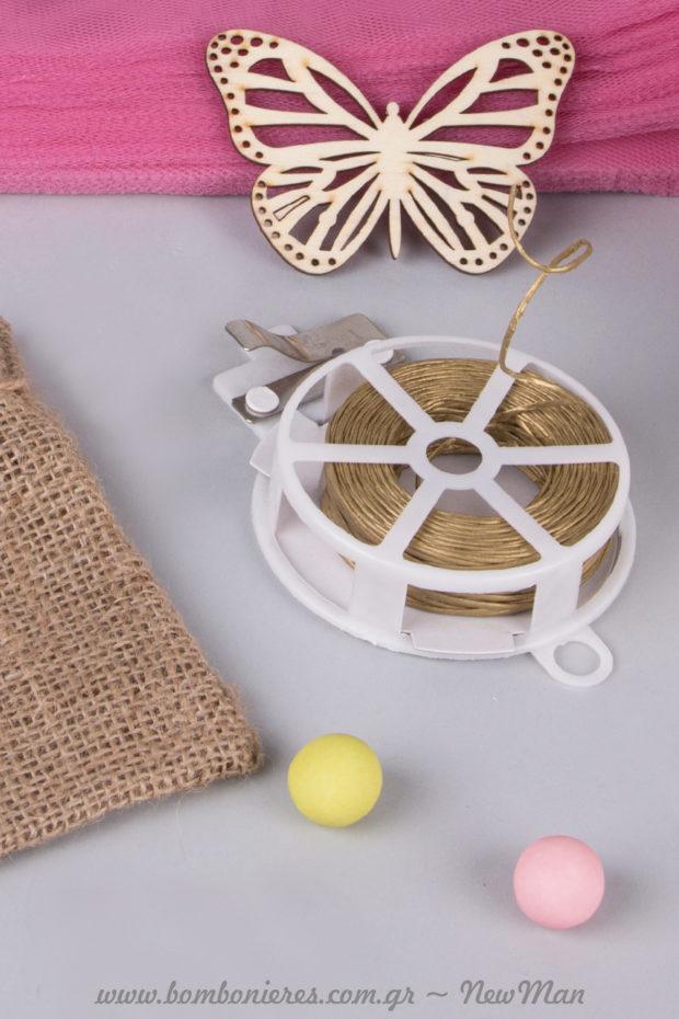 Στερεώστε τη ξύλινη πεταλούδα πάνω στο σώμα της μπομπονιέρας, χρησιμοποιώντας κορδόνι Reffie (σύρμα) σε χρυσαφένια απόχρωση.
