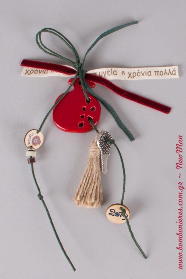 Γούρι με κόκκινο κεραμικό ρόδι διακοσμημένο με πράσινο σπάγκο, βελούδινη κορδέλα, μεταλλικό κλειδί, κορδέλα με ευχές, φούντα και ξύλινα ταμπελάκια-μοτίφ.
