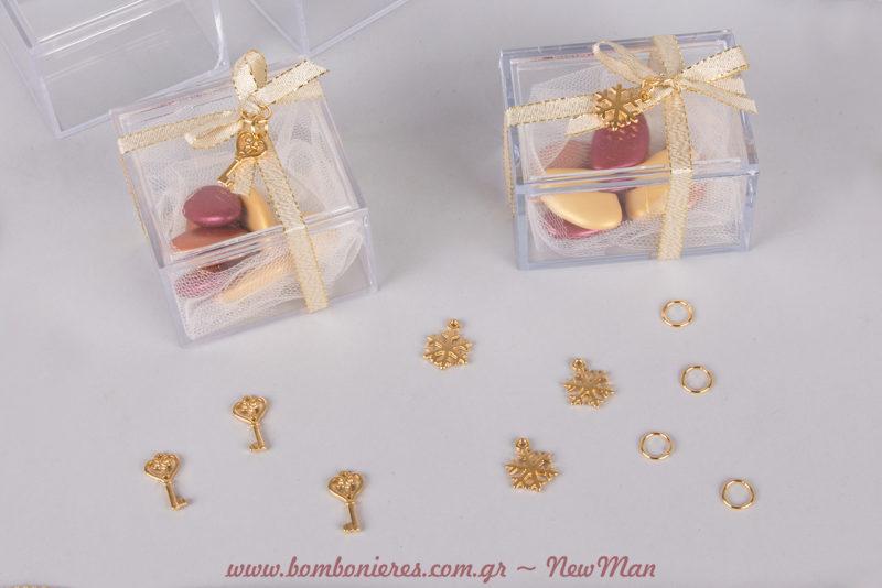 Διάφανη αγάπη, διάφανη μπομπονιέρα σε κουτί, διακοσμημένο με κορδέλα και μεταλλικά διακοσμητικά σε χρυσαφένιες αποχρώσεις.