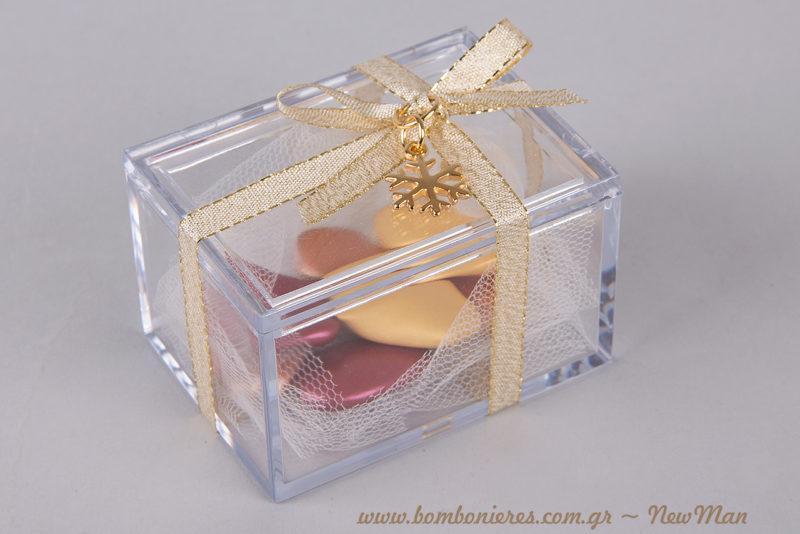 Διάφανη μπομπονιέρα σε παραλληλόγραμμο κουτί, γεμάτη κουφέτα Χατζηγιαννάκης σε μεταλλιζέ αποχρώσεις, διακοσμημένη με κορδέλα χρυσαφένια και χιονονιφάδα.