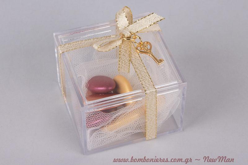 Διάφανη μπομπονιέρα σε τετράγωνο κουτί (65 x 65 x 47mm), διακοσμημένη με κορδέλα μεταλλική ματ και βυζαντινό κλειδί.