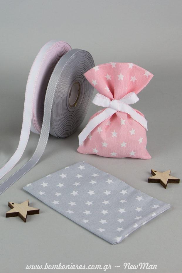 Υφασμάτινο λινό πουγκί με μοτίβο αστέρια σε ροζ ή γκρι, διακοσμημένο με κορδέλα γκρό με γαζί σε αντίστοιχη απόχρωση και ξύλινα αστεράκια σε φυσική απόχρωση.