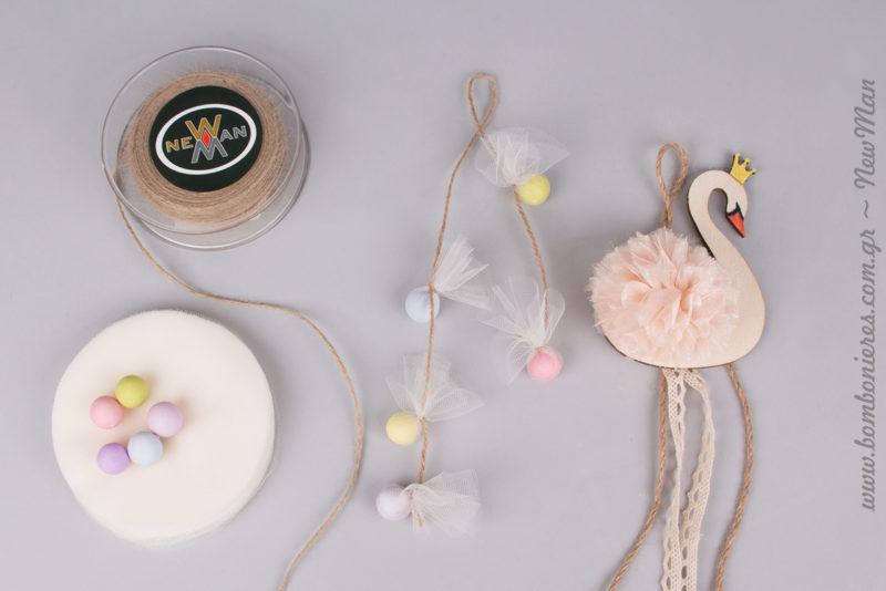 Για τη δημιουργία τους θα χρειαστείτε: ξύλινους διακοσμητικούς κύκνους με πομ-πομ, τούλι ελληνικό, κορδόνι γιούτα ψιλό και κουφέτα Χατζηγιαννάκης.