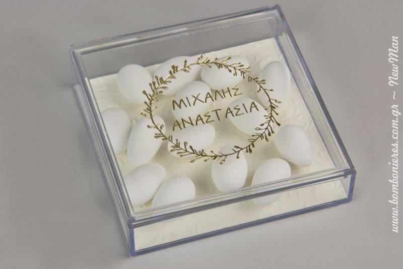 Μπομπονιέρα γάμου σε διάφανο κουτί (100 x 100 x 25mm) με εκτυπωμένα τα ονόματά σας (χρυσό) και διακοσμημένα με χαρτί πολυτελείας & κουφέτα Χατζηγιαννάκης.