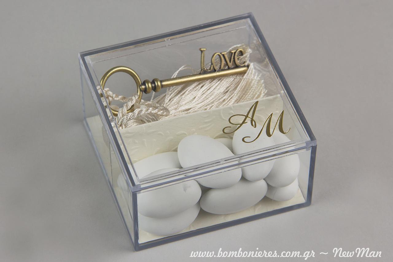 Μπομπονιέρα γάμου σε διάφανο κουτί (80 x 80 x 40mm) με εκτυπωμένα τα αρχικά σας και διακοσμημένη στο εσωτερικό με χαρτί πολυτελείας, κλειδί (love), φούντα σε εκρού χρώμα και κουφέτα.