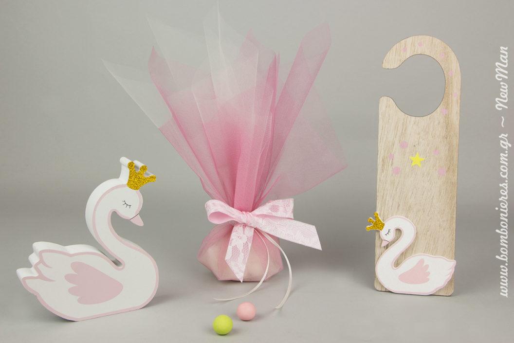 Μια λιτή τούλινη μπομπονιέρα σε ροζ αποχρώσεις και εντυπωσιακά ξύλινα διακοσμητικά Κύκνος για μια βάπτιση σαν παραμύθι.