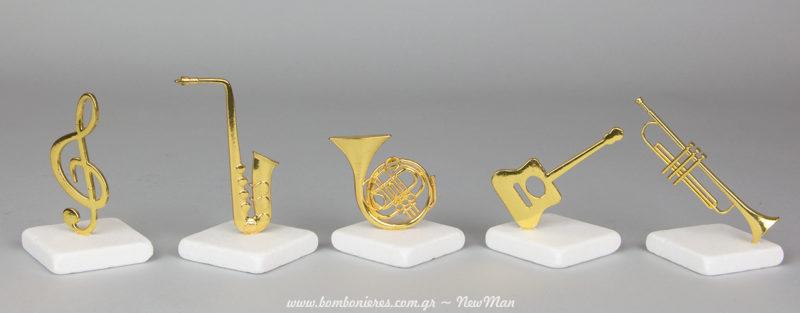 Kleidi tou sol kai metallika mousika organa (klassiki kithara, saksofwno, korno kai trompeta) se lefki petra gia mia mpomponiera pou tha ksexwrisei.