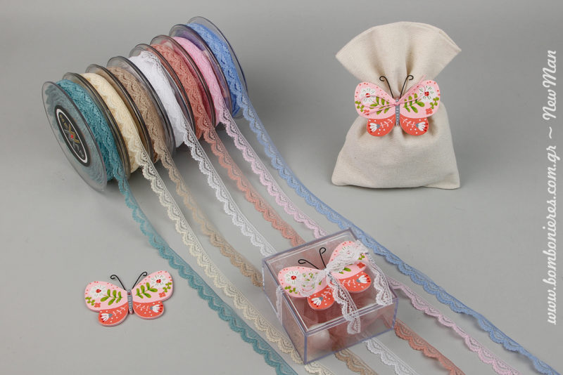 Μπομπονιέρα με θέμα πεταλούδα σε δυο εκδοχές: α) σε διάφανο κουτί συνδυασμένο με δαντέλα Amor και β) σε υφασμάτινο πουγκί συνδυασμένο με κορδόνι πολυεστέρα.