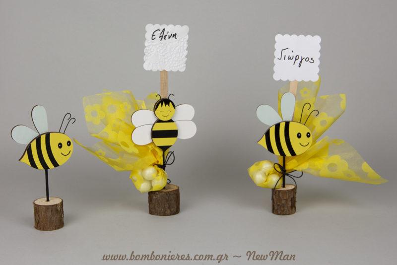 Μπομπονιέρα ξύλινη μελισσούλα σε όρθιο σταντ (15cm), συνδυασμένη με κίτρινη υφασμάτινη βουάλ (27 x 27cm) και κορδόνι κερωμένο σε μαύρο χρώμα.