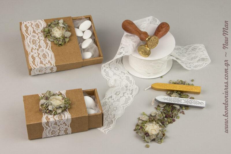Μπομπονιέρα γάμου σε συρταρωτό κουτί kraft, τύπου σπιρτόκουτο, διακοσμημένο με λευκή δαντελένια κορδέλα, σφραγίδα βουλοκέρι και αποξηραμένα λουλουδάκια & βότανα.
